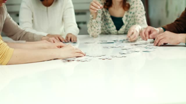 colleagues solving puzzles - puzzle video stock e b–roll