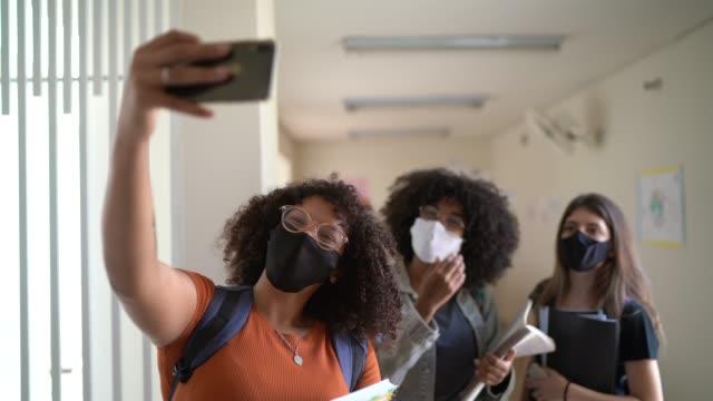 vídeos de stock, filmes e b-roll de colegas tirando uma selfie na escola usando máscara facial - pátio