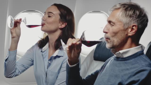 vídeos de stock, filmes e b-roll de colegas brindando taças de vinho em jato particular - primeira classe
