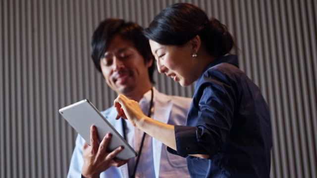 vídeos y material grabado en eventos de stock de colegas con tableta digital en el lobby de la oficina - oficio de ventas