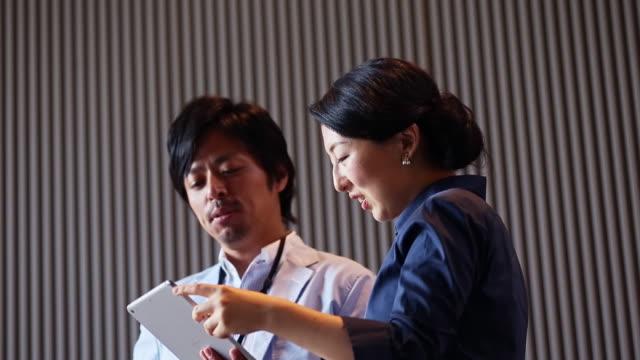 オフィスのロビーでデジタル タブレットを使用して同僚 - ホワイトカラー点の映像素材/bロール