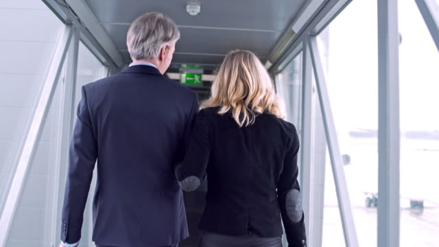 colleagues walking on footbridge at airport - wheeled luggage stock videos and b-roll footage