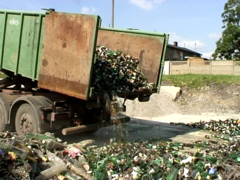 MS, Collection lorry emptying green glass bottles at recycling plant