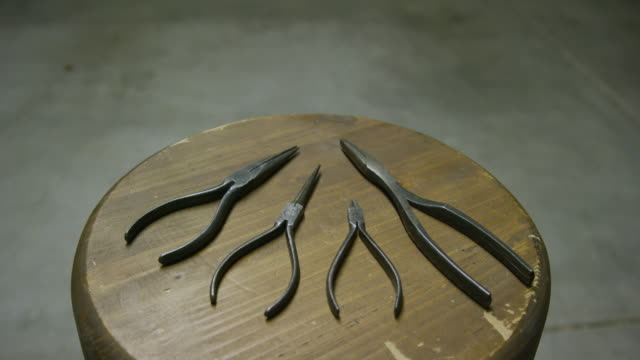 a collection of different sizes of needle nose pliers sit on a wooden stool in an indoor workshop - stool stock videos & royalty-free footage