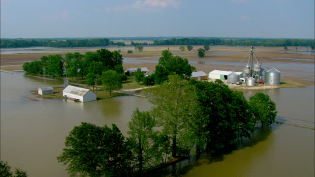 a collection of farm buildings are seen above the flood line. - flood stock videos & royalty-free footage