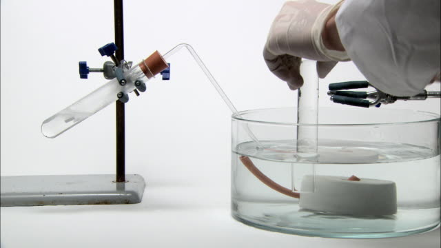 vídeos de stock, filmes e b-roll de collection of hydrogen gas. chemist setting up a water-filled test tube for the collection of hydrogen gas. the gas is produced by the action of hydrochloric acid on magnesium metal in the test tube at left - hidrogênio
