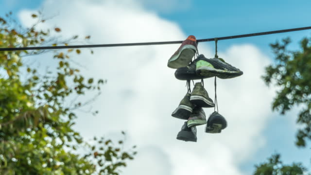 a collection of old trainers hang from a telephone cable after being laced together and thrown over the cable with rapidly moving clouds in the background - 吊るす点の映像素材/bロール