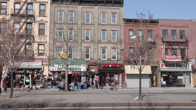 ws collection of shops along local street in harlem / new york, united states - grandangolo tecnica fotografica video stock e b–roll