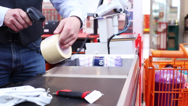 vídeos de stock, filmes e b-roll de collector scans products in a hardware store. - peça de computador