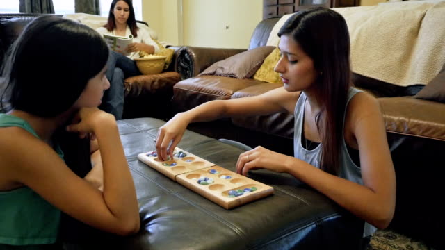 College age young woman playing board game with preteen sister
