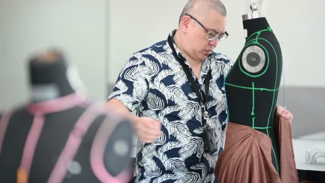 college fashion design lecturer showing his students on the fashion design clothing pin on mannequin - design professional stock videos & royalty-free footage