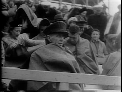 vídeos de stock e filmes b-roll de college football game being played in rain and hail / crowd in stands with umbrellas / navy admiral ernest j king covering himself with rain poncho /... - último quarto de tempo