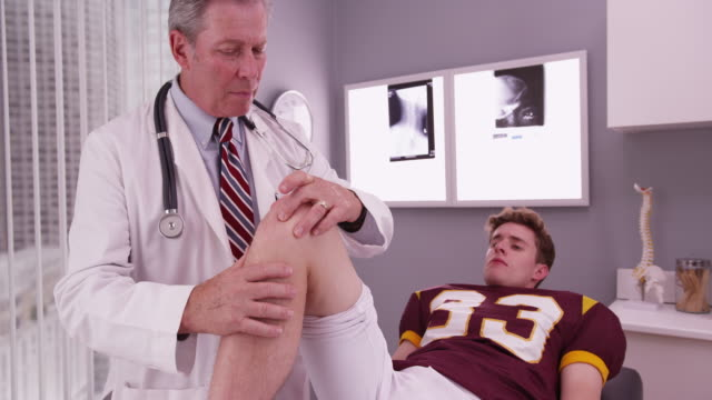 vídeos de stock, filmes e b-roll de college football player having knee injury examined by doctor - physical injury