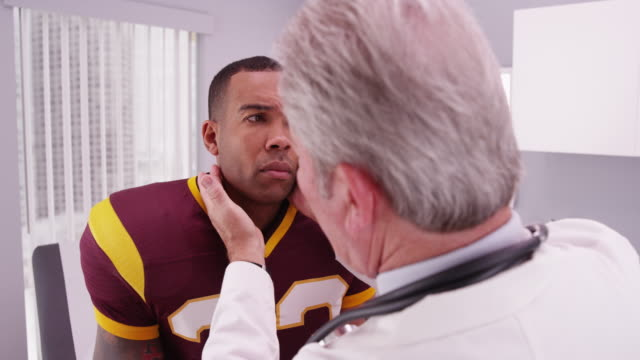 vídeos de stock, filmes e b-roll de college football player having senior doctor review his concussion injury - physical injury