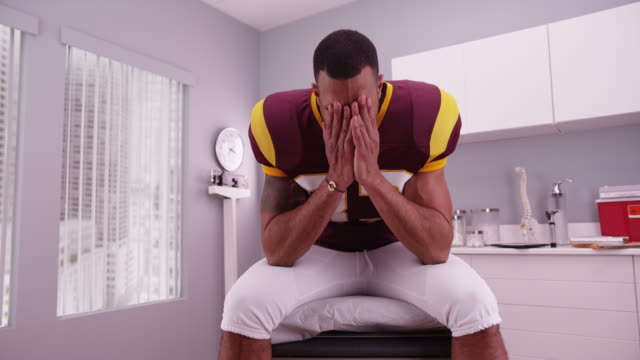 vídeos de stock, filmes e b-roll de college football player waiting in doctor's office for bad news - physical injury