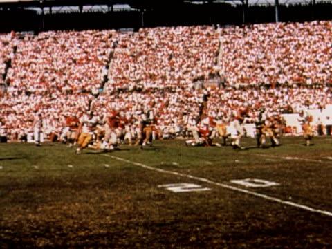 1960 ms college football players making tackle at 20 yard line / usa - アメフトのユニフォーム点の映像素材/bロール