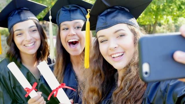 College vrienden maken gezichten terwijl poseren voor selfies na afstuderen