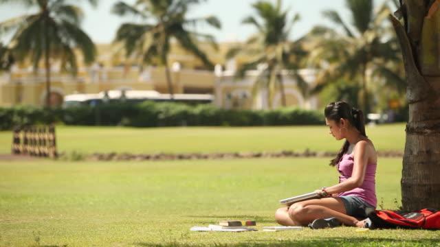vídeos y material grabado en eventos de stock de college girl studying in a park and talking on mobile phone - person in further education