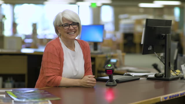 College librarian smiling and talking to students.