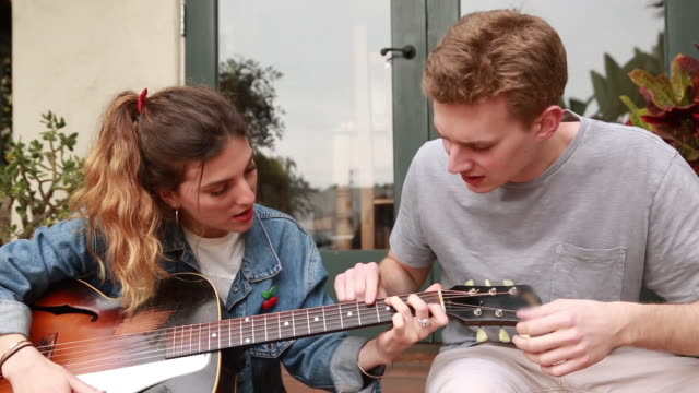 college male teaching guitar to female - gitarre stock-videos und b-roll-filmmaterial