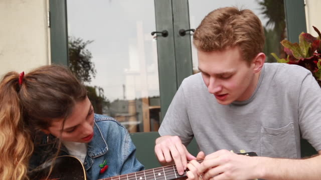 vídeos de stock, filmes e b-roll de college male teaching guitar to female - dedilhando instrumento