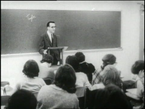 vidéos et rushes de college professor instructs a classroom of young women. - professor
