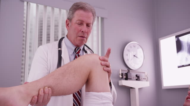 vídeos de stock, filmes e b-roll de college sports athlete with mid aged doctor examining knee injury - physical injury