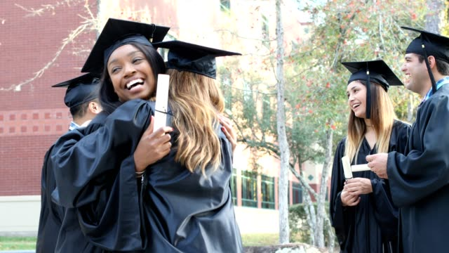 college student friends excitedly hug after graduation ceremony. - adult stock videos & royalty-free footage