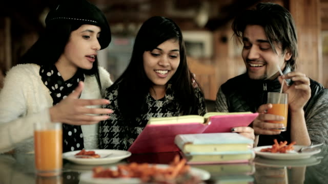 College student vrienden leren en onderwijzen samen in een restaurant.