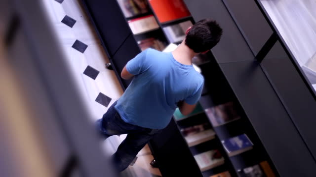 studente nella biblioteca del college - economia video stock e b–roll