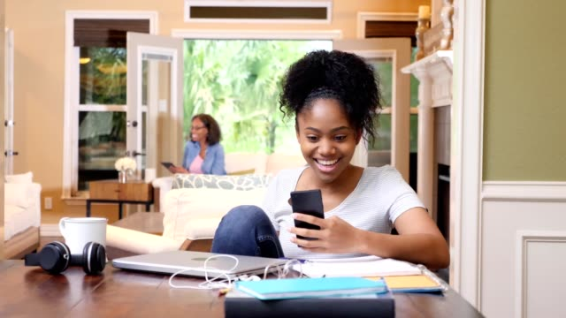 college student laughs while video chatting with friend - curiosità video stock e b–roll