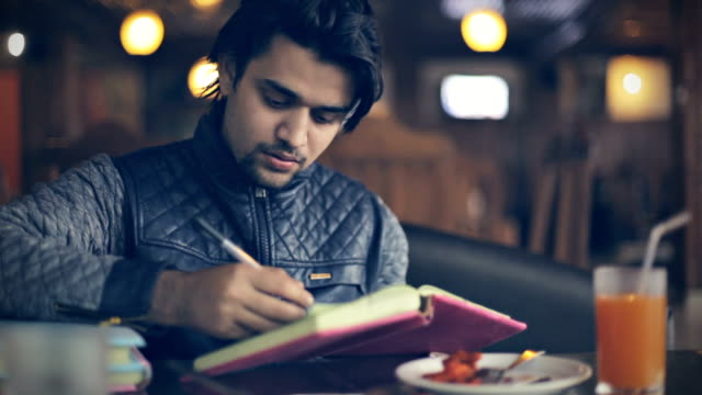 College student studying while eating in restaurant.