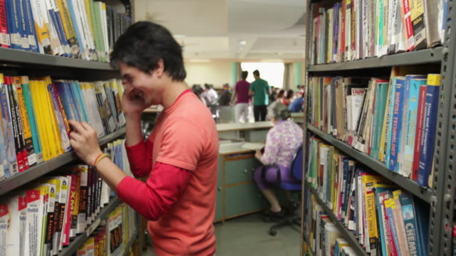 college student talking on a mobile phone in a library - silenzio video stock e b–roll