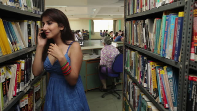college student talking on a mobile phone in a library - indian subcontinent ethnicity stock videos and b-roll footage