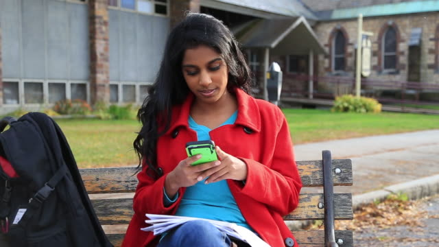 A college student texting on a bench on campus