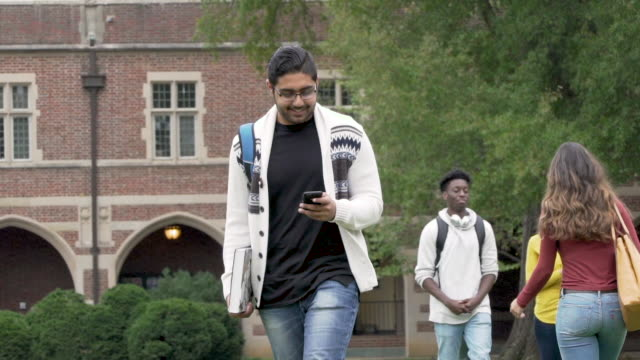college student texting while walking on campus - middle eastern ethnicity stock videos & royalty-free footage