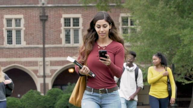 vídeos de stock e filmes b-roll de college student texting while walking on campus - aluno da universidade