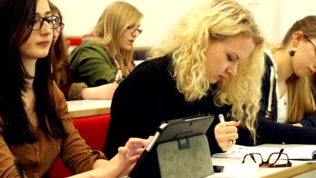 dolly hd, college student using digital tablet in lecture hall - lecture hall bildbanksvideor och videomaterial från bakom kulisserna