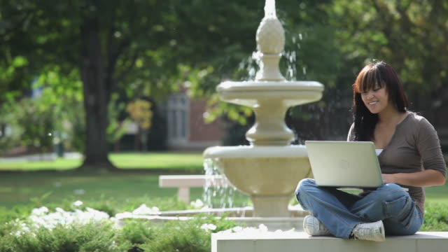ws pan college student using laptop computer in front of fountain in college campus / richmond, virginia, usa  - in front of stock videos & royalty-free footage