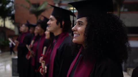 högskolestudenter under sin examensceremoni håller diplom tittar bort stolt och glad - examen bildbanksvideor och videomaterial från bakom kulisserna