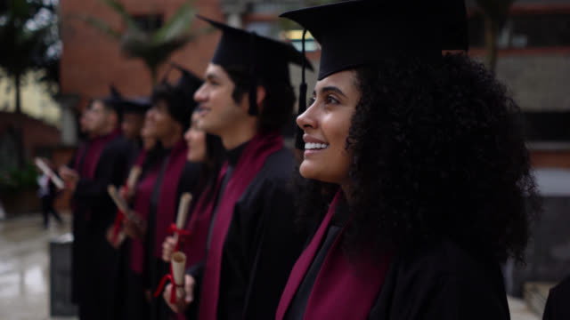 college students during their graduation ceremony holding the diplomas looking away proud and happy - university student stock videos & royalty-free footage