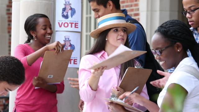 college students encouraging first time voters to register to vote - demokratie stock-videos und b-roll-filmmaterial