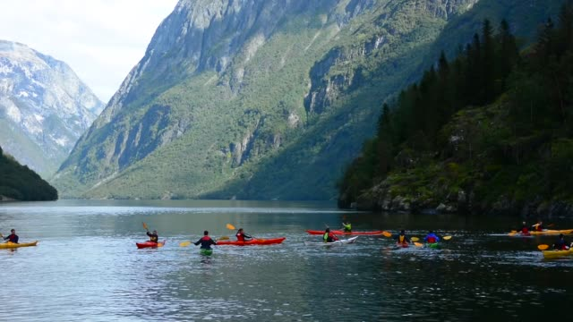 College students getting lesson on paddling colorful kayaks in water