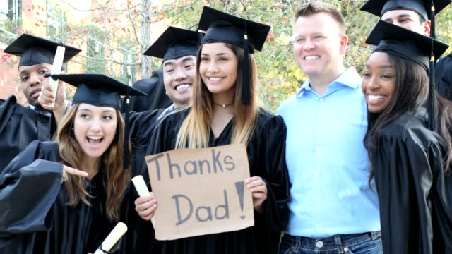 """college students hold """"thanks dad"""" sign after graduation ceremony. - thank you phrase stock videos and b-roll footage"""