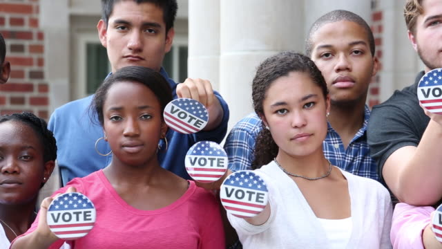 college students holding vote button - demokratie stock-videos und b-roll-filmmaterial