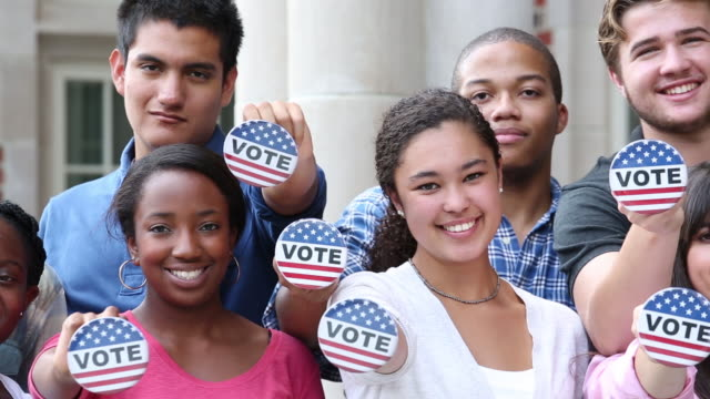 college students holding vote button