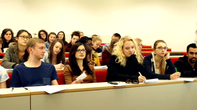 college students passing note in class lecture hall - lecture hall bildbanksvideor och videomaterial från bakom kulisserna