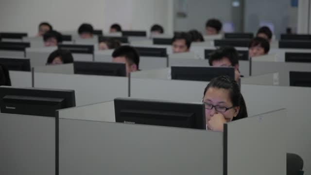 College students read desk monitors as they study in classroom cubicles.