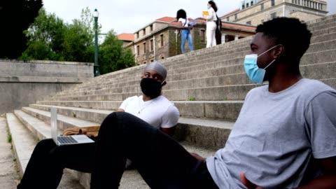 vídeos y material grabado en eventos de stock de los estudiantes universitarios regresan al campus universitario con máscaras protectoras - cuatro personas