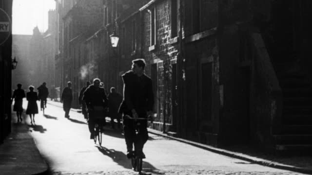 montage college students riding bicycles in alley, student removing bike from rack and riding off, students in academic gowns entering university / st. andrews, scotland, united kingdom - 1948 stock-videos und b-roll-filmmaterial